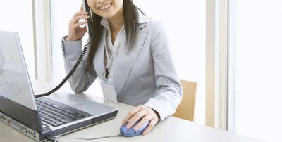 partial image of woman on the phone at computer