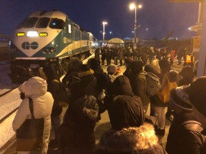 GO transit customers stand on the platform as a train approaches.