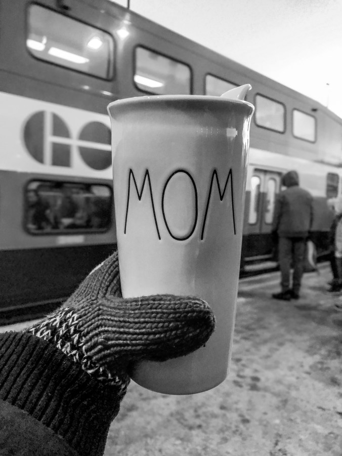 A mitted hand holds up a coffee cup with 'Mom' written on it