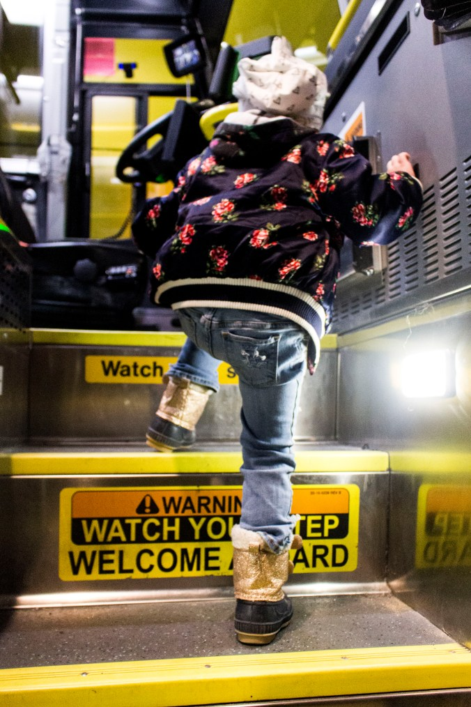 A young girl struggles to climb the stairs into the GO bus.