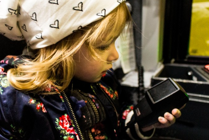 A small child talks into the mic used on the GO bus.