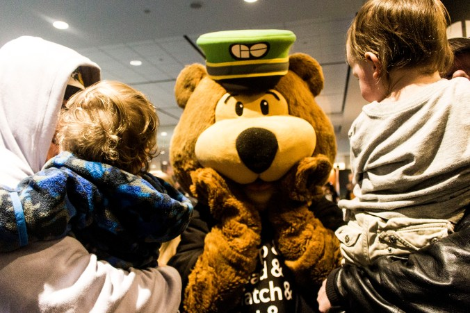 Two small children get up close to meet GO Bear, the fuzzy bear mascot for GO.