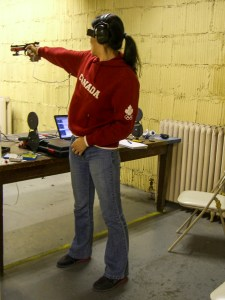 A woman practices her stance, while in front of a table. Her back is to the camera.