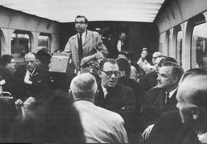 Men in suits and ties sit next to one another on a packed GO train. One man tries to squeeze past them as he walks down the aisle.