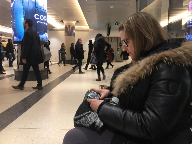 Maja Cupples is shown sitting on a bench, looking at her phone. Behind her, in Union Station, other customers rush by, heading to their final morning destinations.