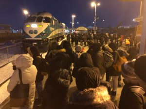 Crowds of customers, bundled up, wait in lines as a train arrives at Bramalea GO station.