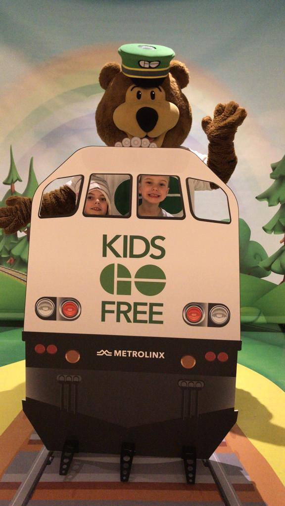 Two children post behind a cutout of a GO train.