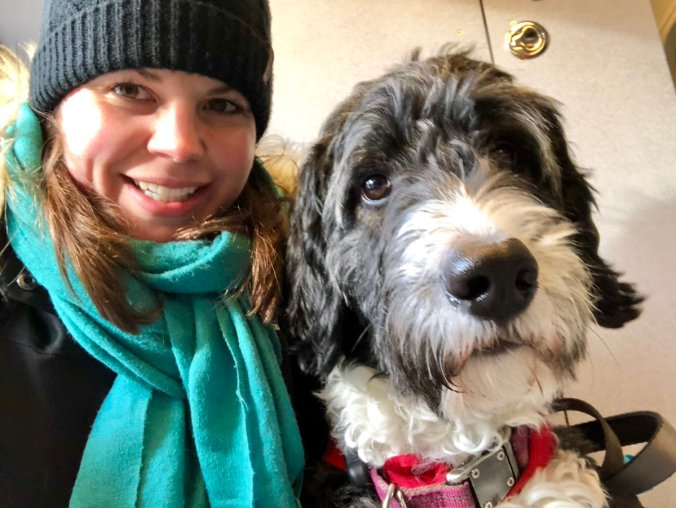 Jennifer Minelli smiles at the camera as she poses up next to her black and white, larger dog Aubree.