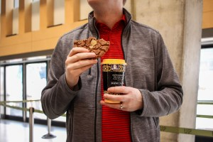 Photo of a customer at Balzacs coffee with a coffee cup and cookie.