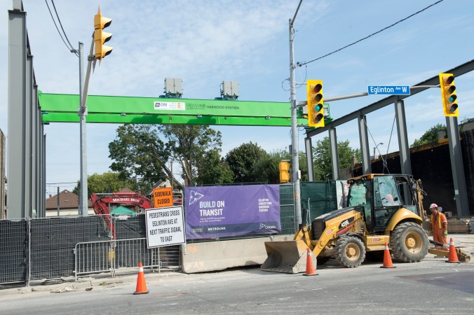 Rather than a high crane, a lowe-level green gantry system sits directly over the construction hole.