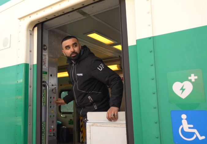 GO Transit Customer Service Ambassador Zohaib Khan looks out from the GO Train as he prepares to close the train doors.