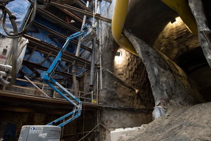 A crane works inside a massive cavern that's been dug out below an active part of the city. Shown are concrete and earth walls, circling platforms and machines.