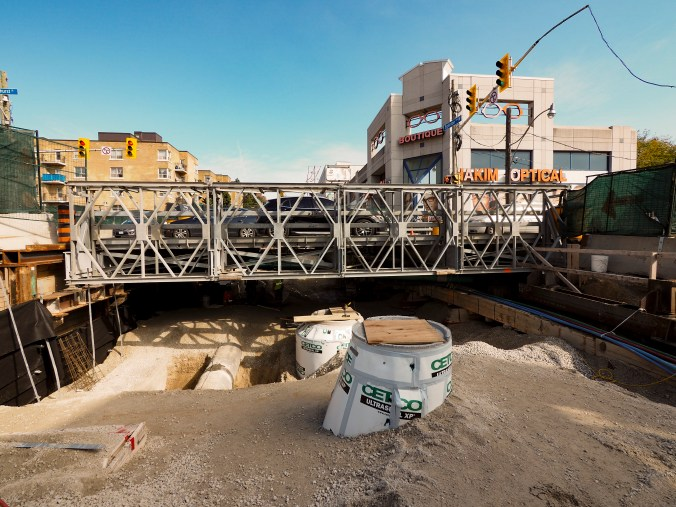 Local traffic is seen crossing over a small bridge span. Under it, construction continues.