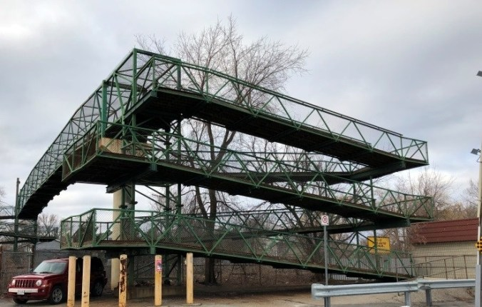 The bridge is shown, with its large green metal zig-zag stairs and small pathway over the rails.