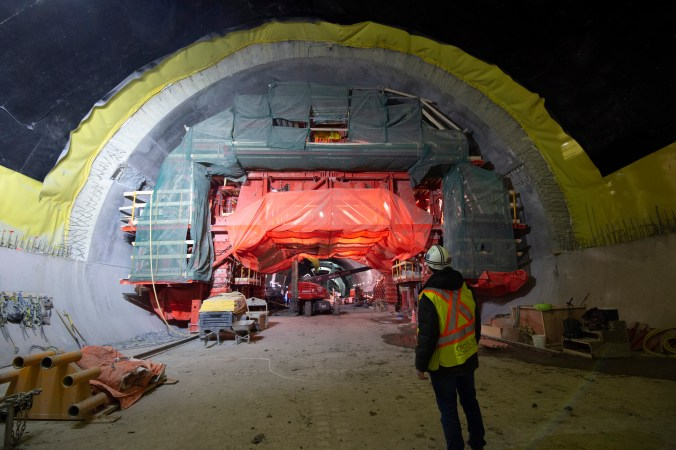 A workman looks at a large concrete tunnel, with equipment working inside.