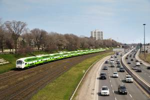 A GO train is shown going down the tracks, as cars drive on nearby Lakeshore Drive, in Toronto.