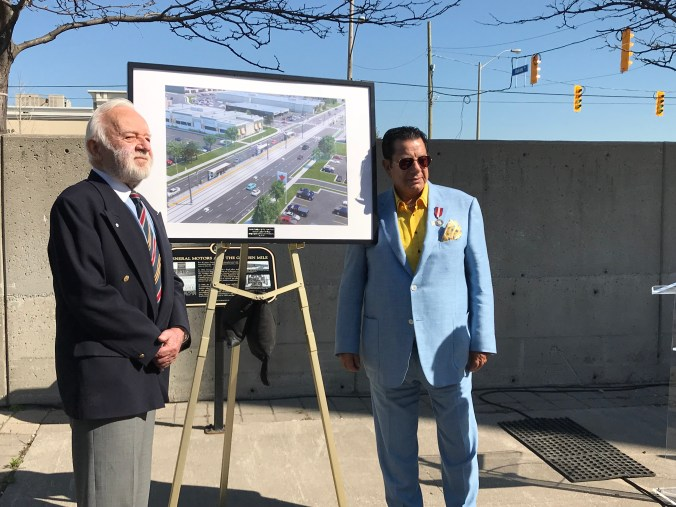 Joseph Lebovic and Karim Hakimi are shown posing next to an artist concept of the stop named after them.