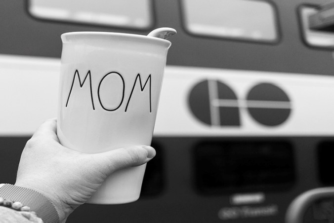 Image shows someone holding up a coffee cup next to a GO train.