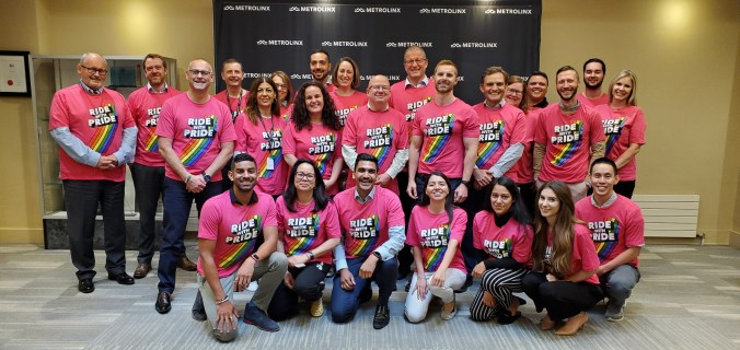 Team members pose for the camera in Ride with Pride T-shirts.