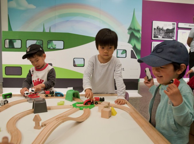 Three children play with cars and a wooden roadway on an activity table.