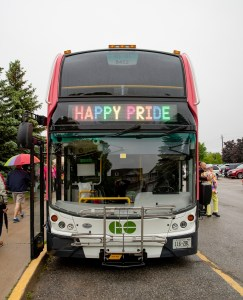 A GO bus diplays 'Happy Pride' across the destination message, above the driver.