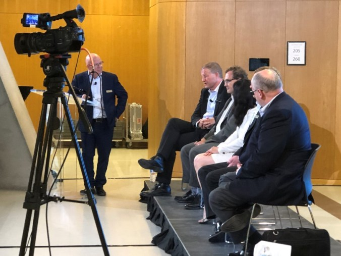 Members of the senior management team sit on a podium, looking at Phil Verster, as he answers a question from the audience.