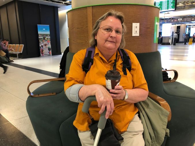 Karen sits inside Union Station, holding a cup of coffee.