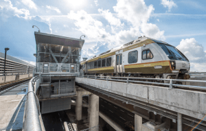 An UP Express train heads out of the Toronto airport, as the sun shines bright above.