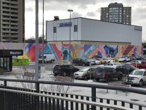 A wall mural is shown by the Weston station and parking lot.