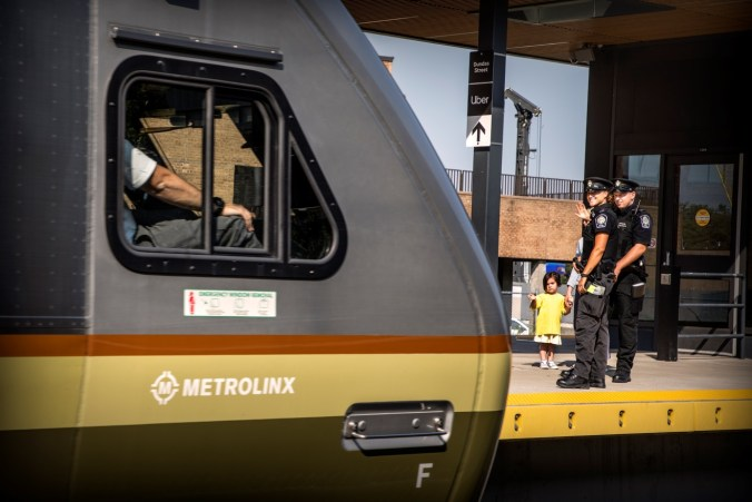 Officers stand with children as an UP Express train arrives.