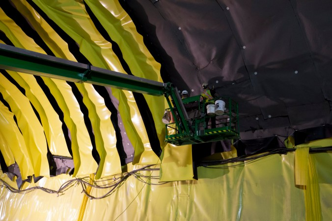 Crews work to install yellow waterproofing strips on the inside of the Avenue Station tunnel.