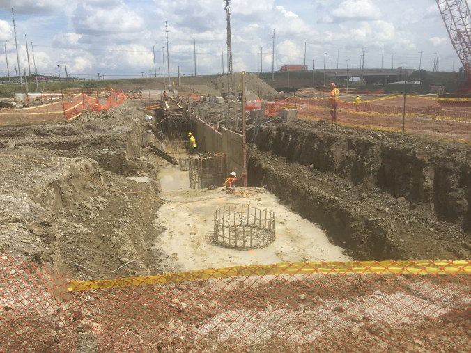 Crews work within a construction pit.