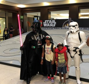 Children stand next to Star Wars characters.