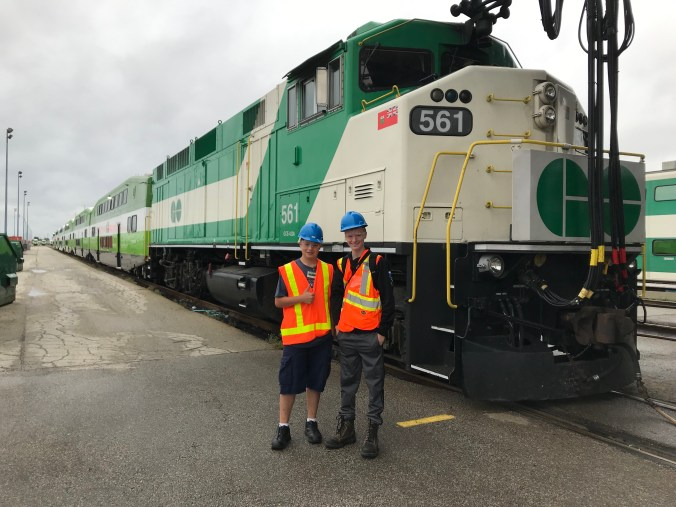 The two teens stand next to a large GO train while on a recent visit to the Wilowbrook facility.