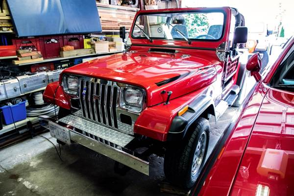 A red Jeep sits parked in a garage.