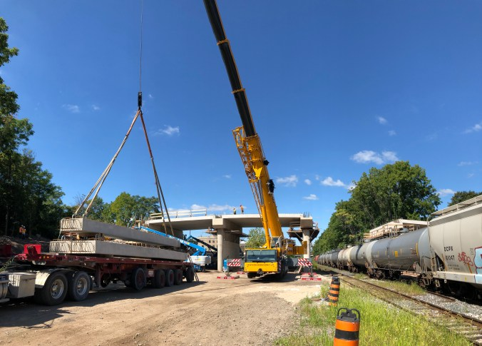 A massive crane lifts a piece of concrete into place during the widening work on the John Street Bridge in Hamilton.
