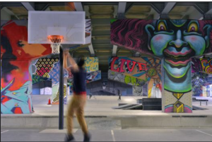 A man plays basketball under a Don Valley elevated guideway.