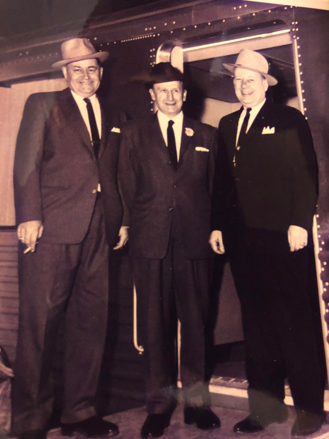 Three men in suits and hats pose in front of a train door.