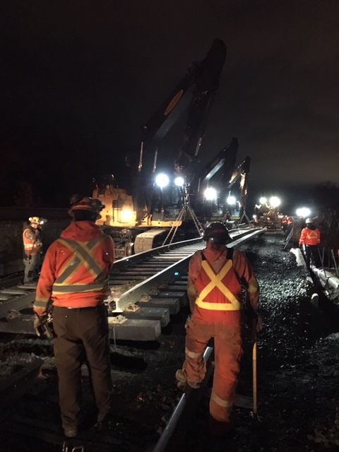 Crews work at night along a section of track.