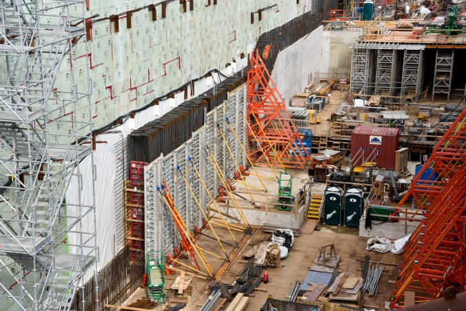 Metal supports are shown shoring up a wall, down in a deep construction pit.