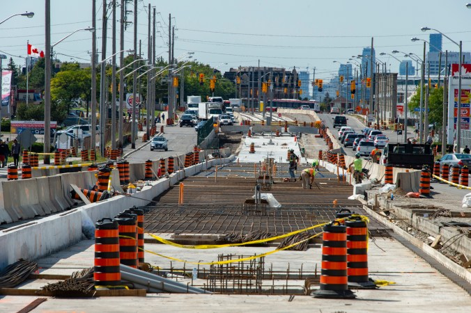 Photo of construction at street level on the Eglinton Crosstown LRT tracks and concrete being installed for the tracks.