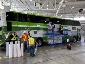 Crews stick vinyl panels onto the side of a GO bus.