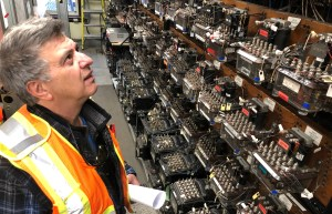 Vito stares up at electrical components, as he holds a paper in his hand.