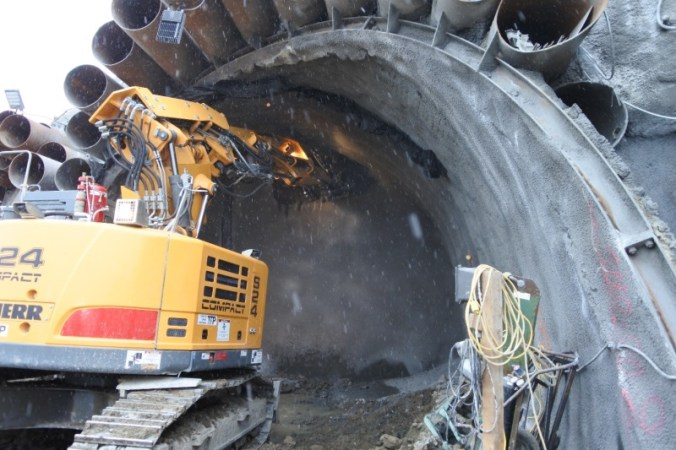 Image shows a large machine digging into the tunnel.