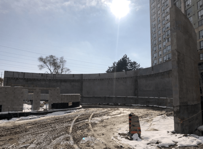 Image shows a concrete wall, with a large apartment just behind.