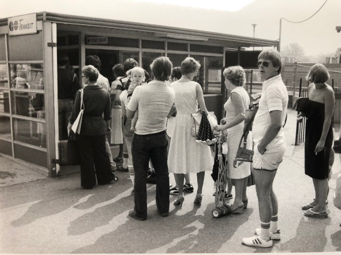 Image shows a long line of transit customers, waiting to buy tickets.