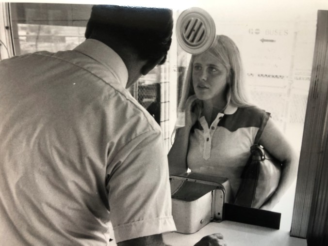 A woman stands in front of a ticket agent.