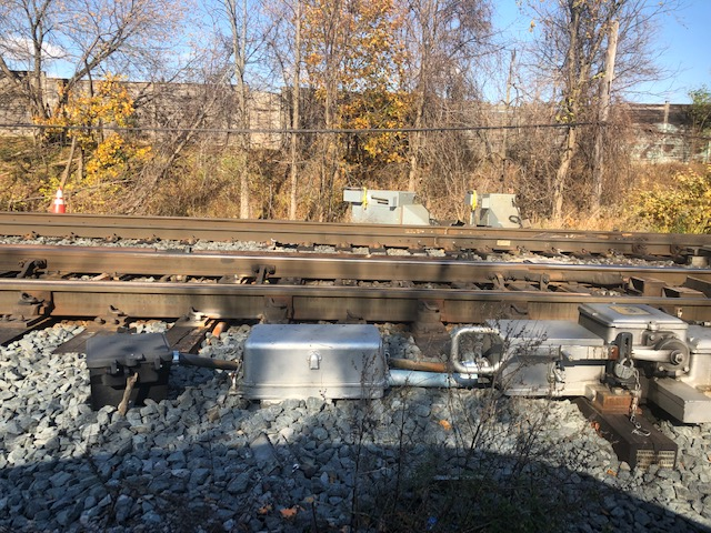 A photo of rail switch infrastructure next to the tracks.