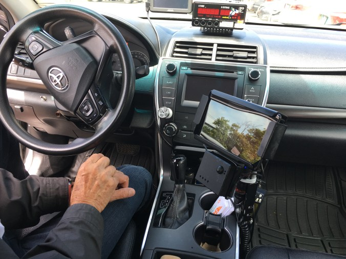 A driver sits in his vehicle, beside a payment system.