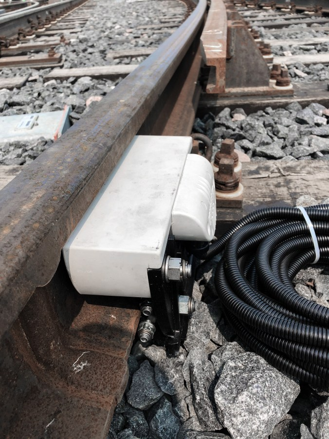 Image shows a small white electrical box, attached to the rails.